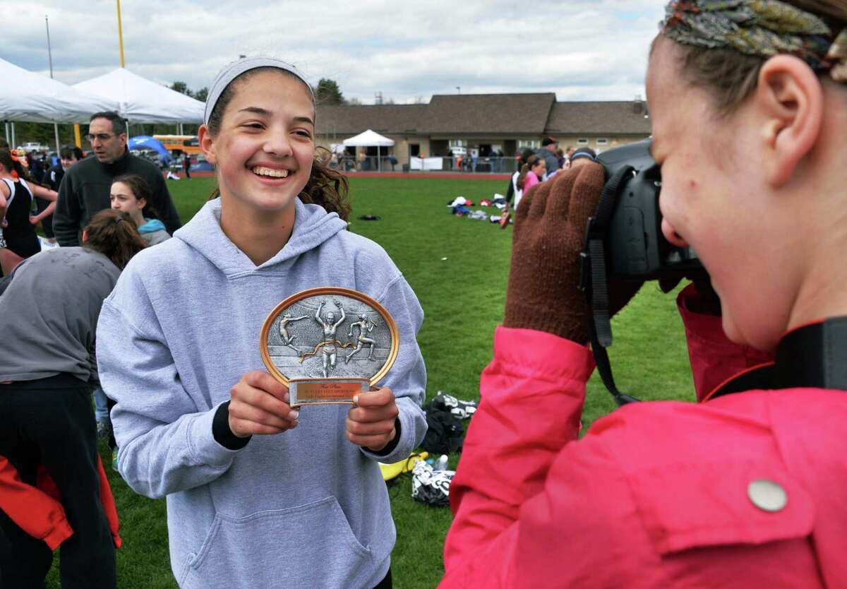Guilderland's Abby Marco, left, is photographed by her team manager Jo Ann Mulligan after winning the 100m hurdles during the Lady Eagle Invitational outdoor track meet at Bethlehem High School in Delmar, N.Y. Saturday April 20, 2013. (John Carl D'Annibale / Times Union)
