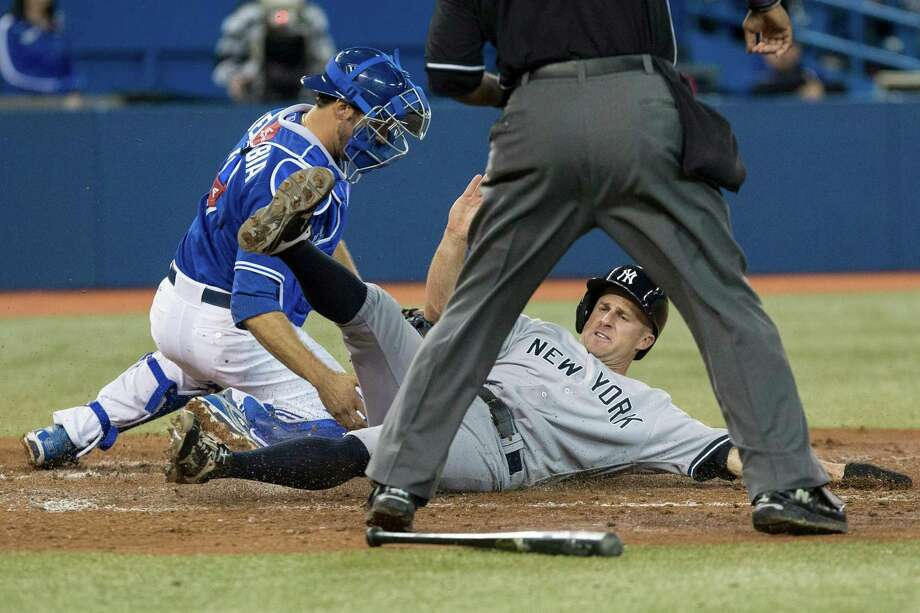 New York Yankees' Brett Gardner slides safely into home in front of Toronto Blue Jays catcher J.P. Arencibia after a two-run single from Kevin Youkilis in the fifth inning of a baseball game in Toronto on Saturday, April 20, 2013. (AP Photo/The Canadian Press, Chris Young) Photo: Chris Young
