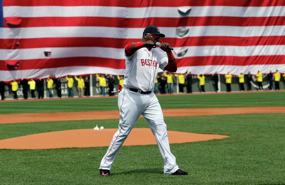 Boston Red Sox's David Ortiz pumps his fist in front of an Amarican flag and a line of Boston Marathon volunteers, background, after addressing the crowd before a baseball game between the Boston Red Sox and the Kansas City Royals in Boston, Saturday, April 20, 2013. (AP Photo/Michael Dwyer) Photo: Michael Dwyer