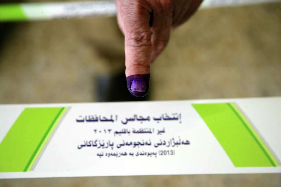 An internally displaced Iraqi shows his ink-stained finger, indicating he cast a ballot, at a polling station in the northern Iraqi Kurdish city of Arbil Photo: Safin Hamed / AFP / Getty Images