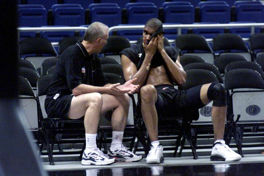 Spurs\' Tim Duncan (right) wipes sweat from his face as head coach Gregg Popovich talks with him after practice at the Alamodome on Thursday, April 27, 2000. Duncan is expected to return in time to play in the third playoff game against the Phoenix Suns. Kin Man Hui/Express-News