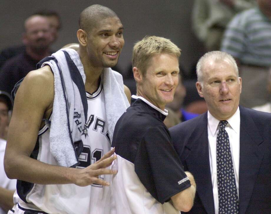 Spurs forward Tim Duncan (21) guard Steve Kerr, center, and coach Gregg Popovich enjoy the final minutes of game 2 of the Western Conference finals against the Dallas Mavericks in San Antonio, Wednesday, May 21, 2003. San Antonio won, 119-106. (AP Photo/Eric Gay)
