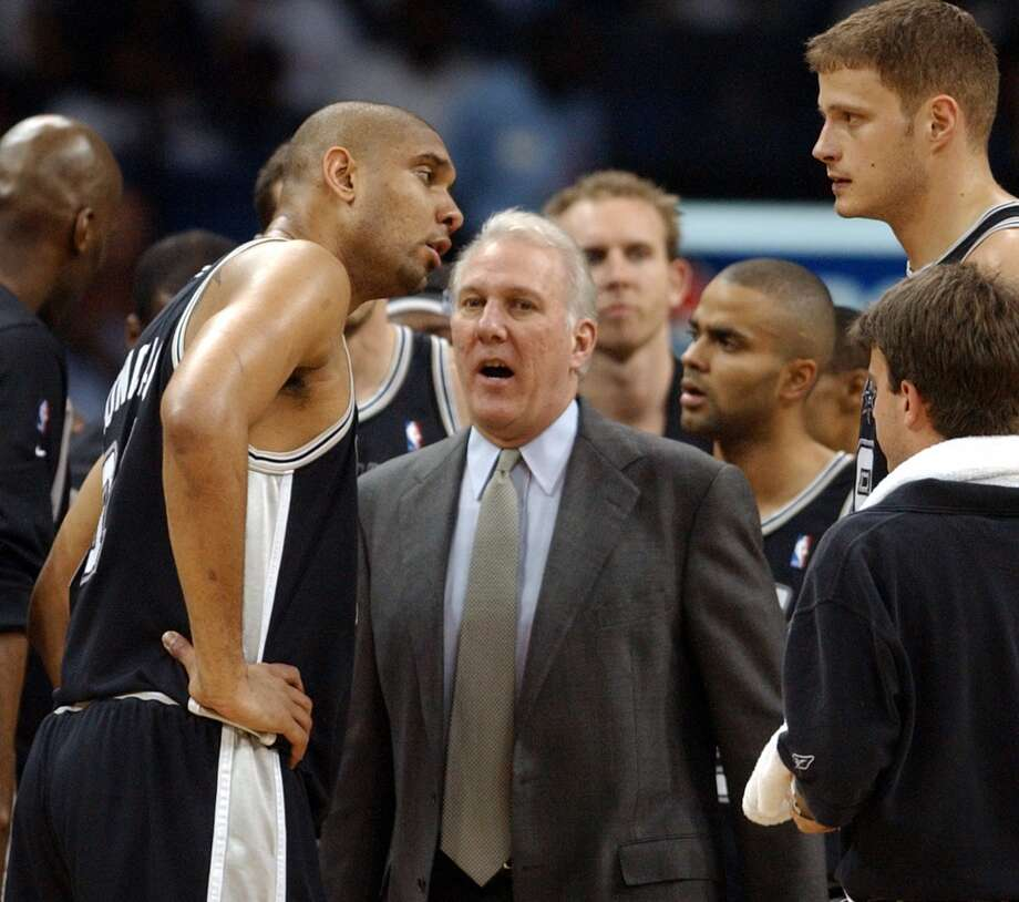 Spurs\' Tim Duncan talks with coach Gregg Popovich as Rasho Nesterovic listens during a timeout against the Grizzlies Sunday April 25, 2004 during Game 4, Round 1 of the 2004 NBA Playoffs at the Pyramid in Memphis, TN. The Spurs went on to win 110-97.  EDWARD A. ORNELAS/Express-News