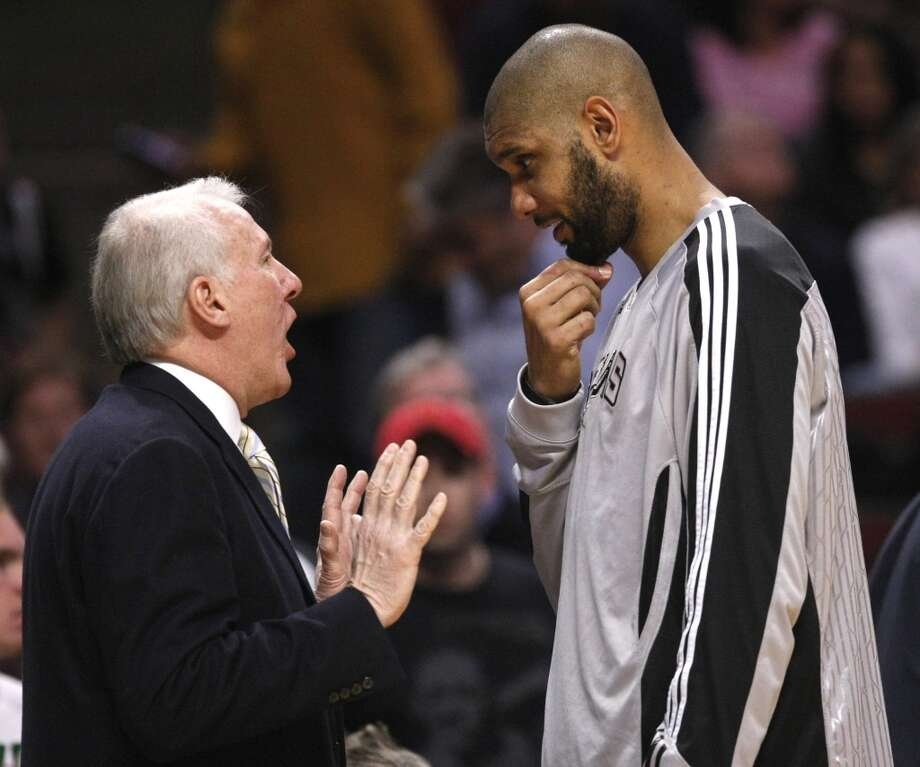 Spurs head coach Gregg Popovich, left, talks with center Tim Duncan during the first half of an NBA basketball game against the Chicago Bulls, Thursday, Feb. 17, 2011, in Chicago. (AP Photo/Charles Rex Arbogast)