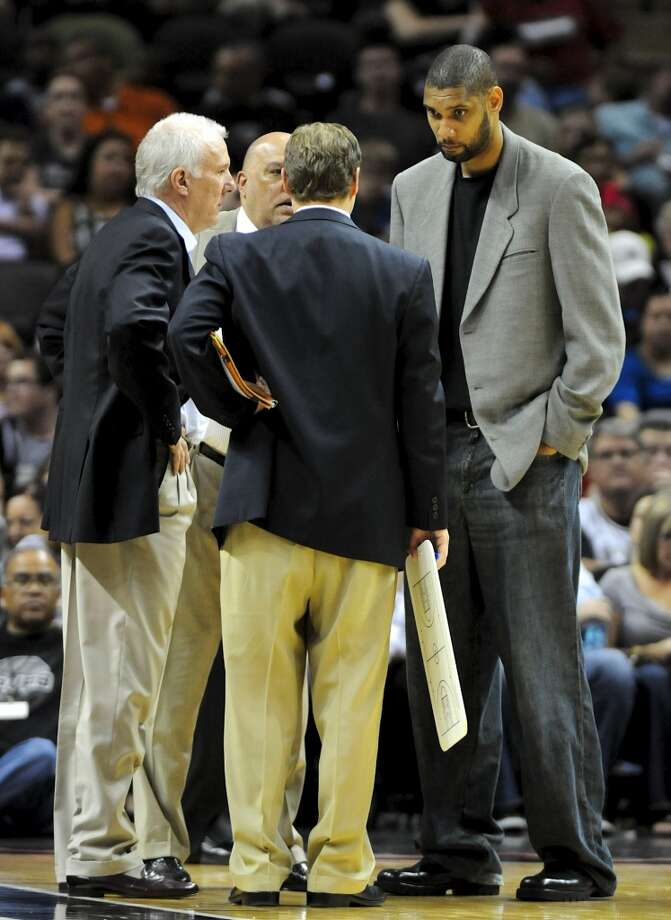 Spurs center Tim Duncan (right) joins San Antonio coach Gregg Popovich (left) and the assistant coaches on the floor during a time out during a NBA basketball game between the Philadelphia 76ers and the San Antonio Spurs at the AT&T Center in San Antonio, Texas on March 25, 2012. Duncan sat out Sunday\'s game against the 76ers. John Albright / Special to the Express-News.