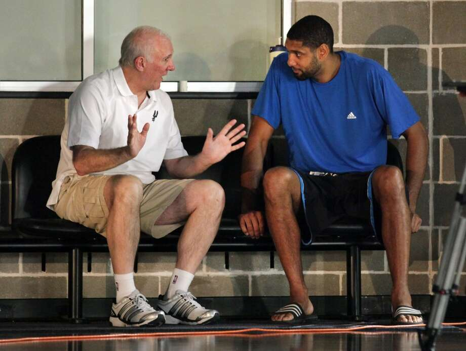 The San Antonio Spurs Coach Gregg Popovich, left, talks with Tim Duncan during a break from taking photos during media day at the team's practice facility.  Oct. 1, 2012.