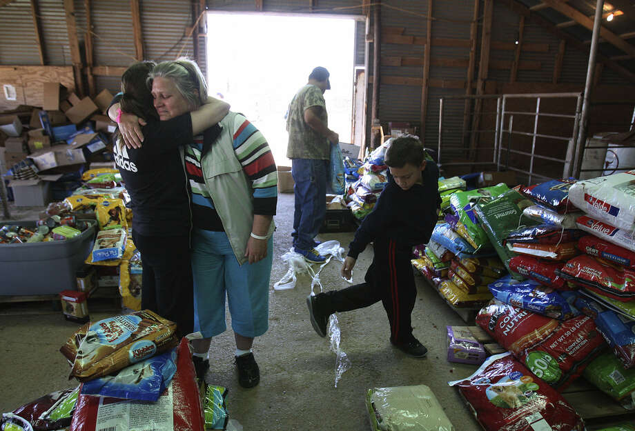 Jacki Arias (second from left) receives a hug from a neighbor named Mindy while picking up pet food for the cat they had to leave at home when they fled the fertilizer plant explosion in West. Arias' family has been staying with relatives since then. Photo: Kin Man Hui / San Antonio Express-News