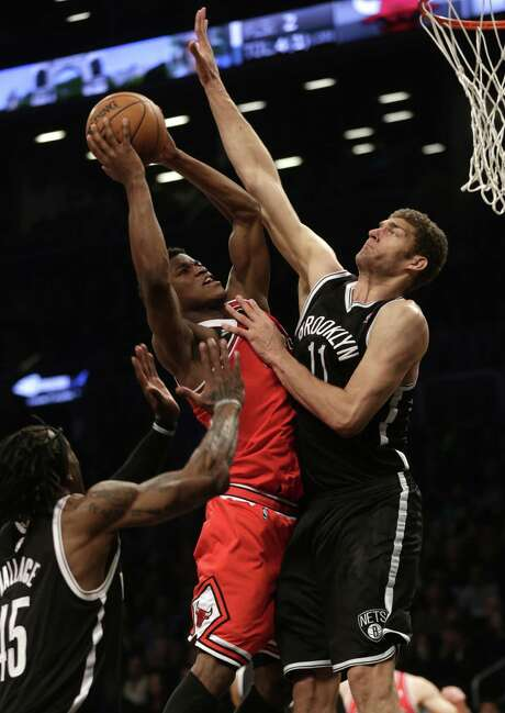 The Nets' Brook Lopez (right) blocks Jimmy Butler. Lopez scored 21 points for Brooklyn. Photo: Seth Wenig / Associated Press