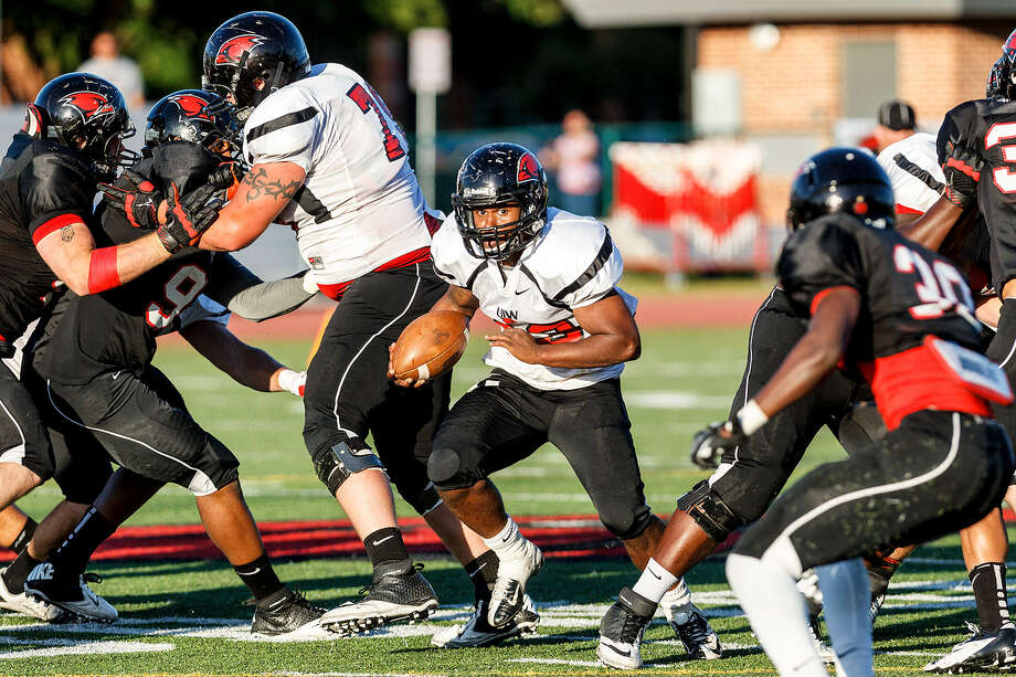 Cardinals sophomore running back Dorian Williams sprints through an opening in the defensive line Saturday at Benson Stadium.