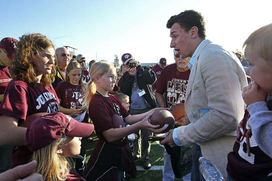 Johnny Manziel, Texas A&M's Heisman Trophy-winning quarterback who led the Aggies to an 11-2 record last season, signs autographs for fans after Saturday's ceremony welcoming him home at Antler Stadium. Photo: Photos By Tom Reel / San Antonio Express-News