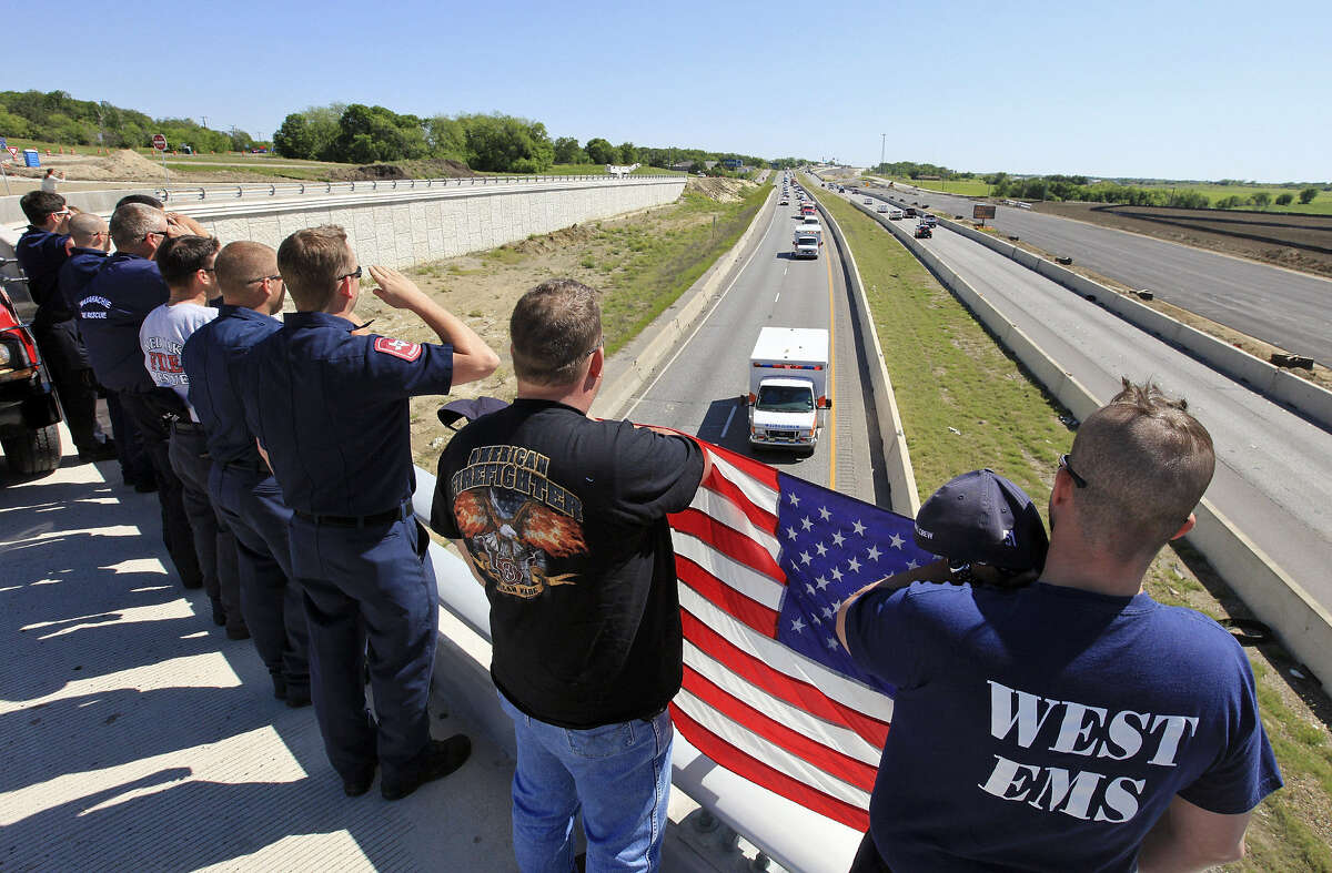 """First responders pay tribute to their fallen """"brothers"""" as their remains are driven to Dallas."""