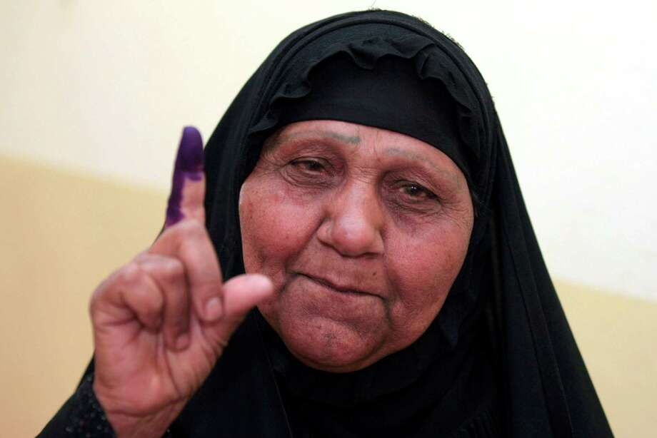 Iraq on Saturday held its first successful election since the U.S. military withdrawal. Citizens dip their fingers in purple ink at the polls to prevent repeat voting. Photo: Karim Kadim, STF / AP