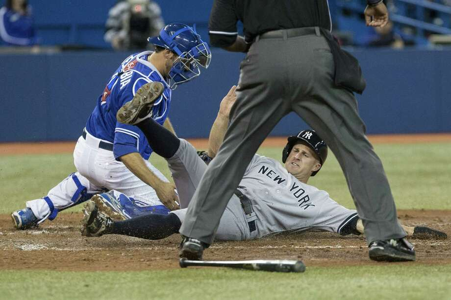 New York's Brett Gardner scores ahead of a tag by Toronto's J.P. Arencibia in the fifth inning Saturday. Photo: Chris Young / Associated Press