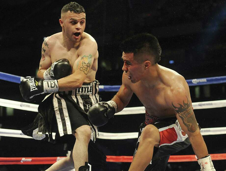 Omar Gonzales (left) scores a knockdown of the favored Raul Martinez in a preliminary bout on Saturday night's boxing card at the Alamodome. Photo: Billy Calzada / San Antonio Express-News