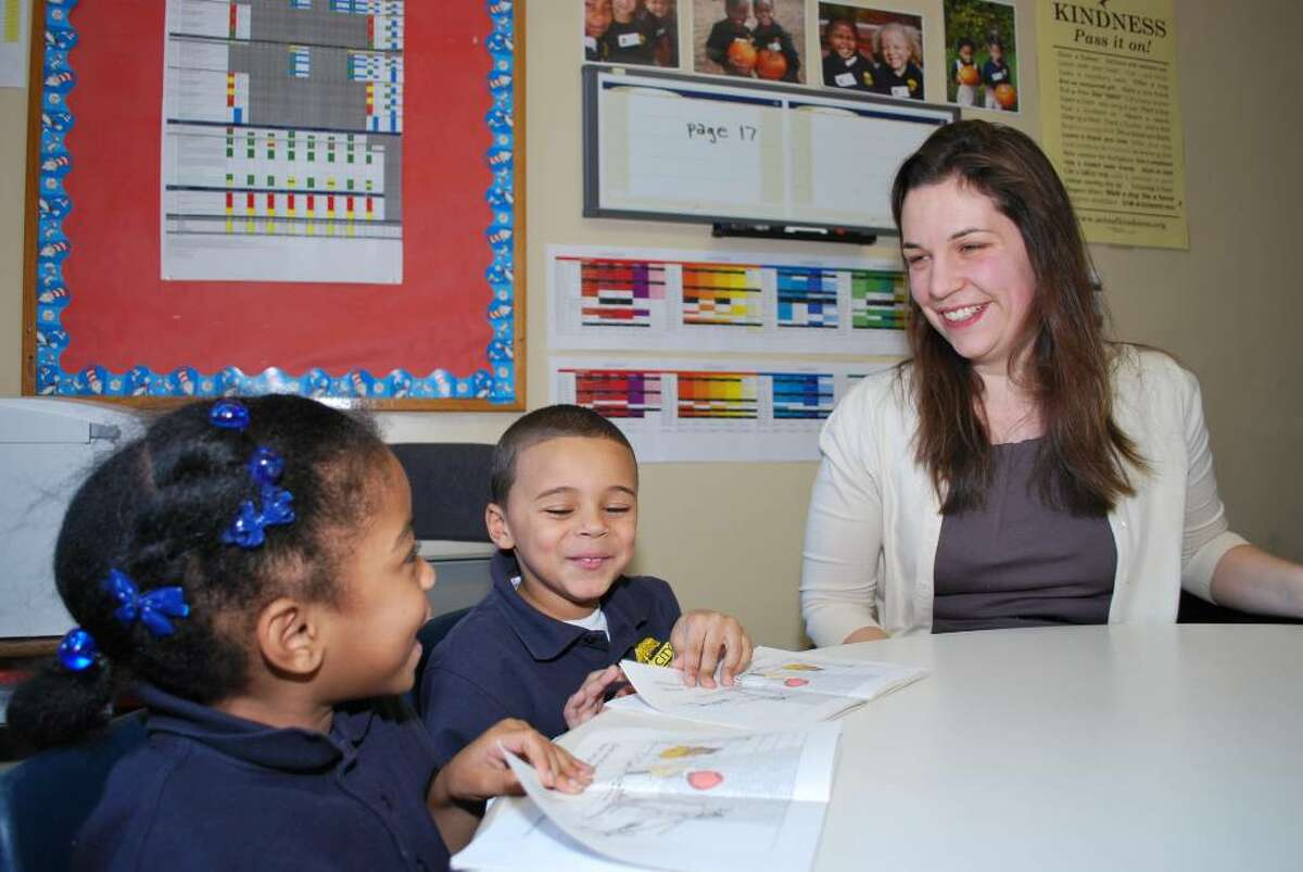 Katherine Baker, the new principal of Achievement First Bridgeport Academy Elementary, works with Elm City Prep students Kristian Morales and Emorej Hunter. Elm City Prep is the the New Haven charter elementary run by Achievement First.