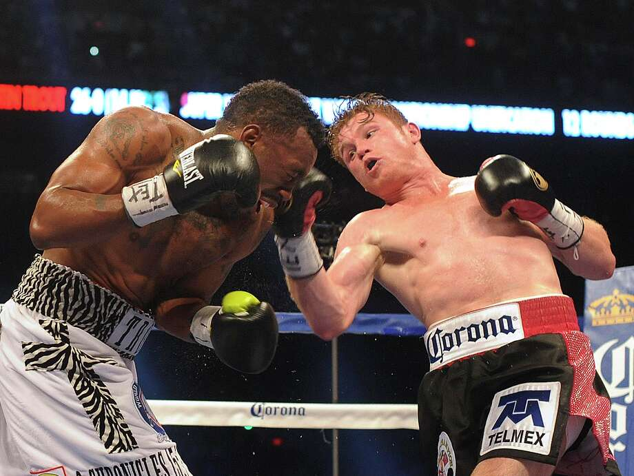 "Saul ""Canelo"" Alvarez connects to the head of Austin Trout during their 154-pound boxing title unification bout in the Alamodome on Saturday, April 20, 2013. Photo: Billy Calzada, Express-News / San Antonio Express-News"