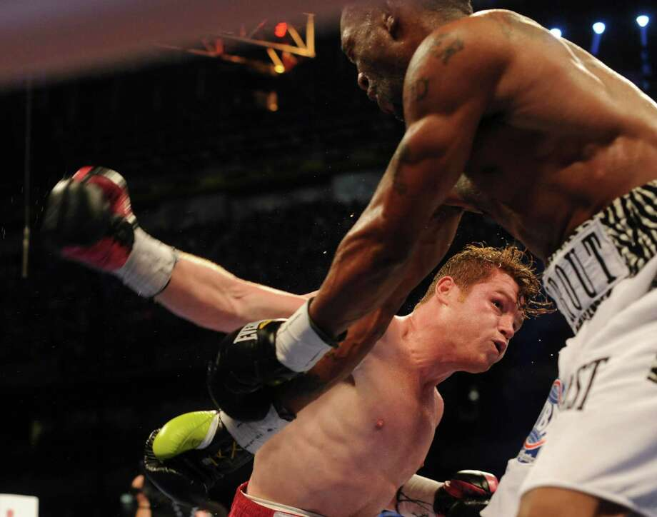 "Saul ""Canelo"" Alvarez swings at Austin Trout during their 154-pound boxing title unification bout in the Alamodome on Saturday, April 20, 2013. Alvarez won the fight. Photo: Billy Calzada, Express-News / San Antonio Express-News"