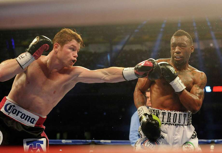 "Saul ""Canelo"" Alvarez, left, reaches for Austin Trout during the 1st round of their 154-pound boxing title unification bout in the Alamodome on Saturday, April 20, 2013. Photo: Billy Calzada, Express-News / San Antonio Express-News"