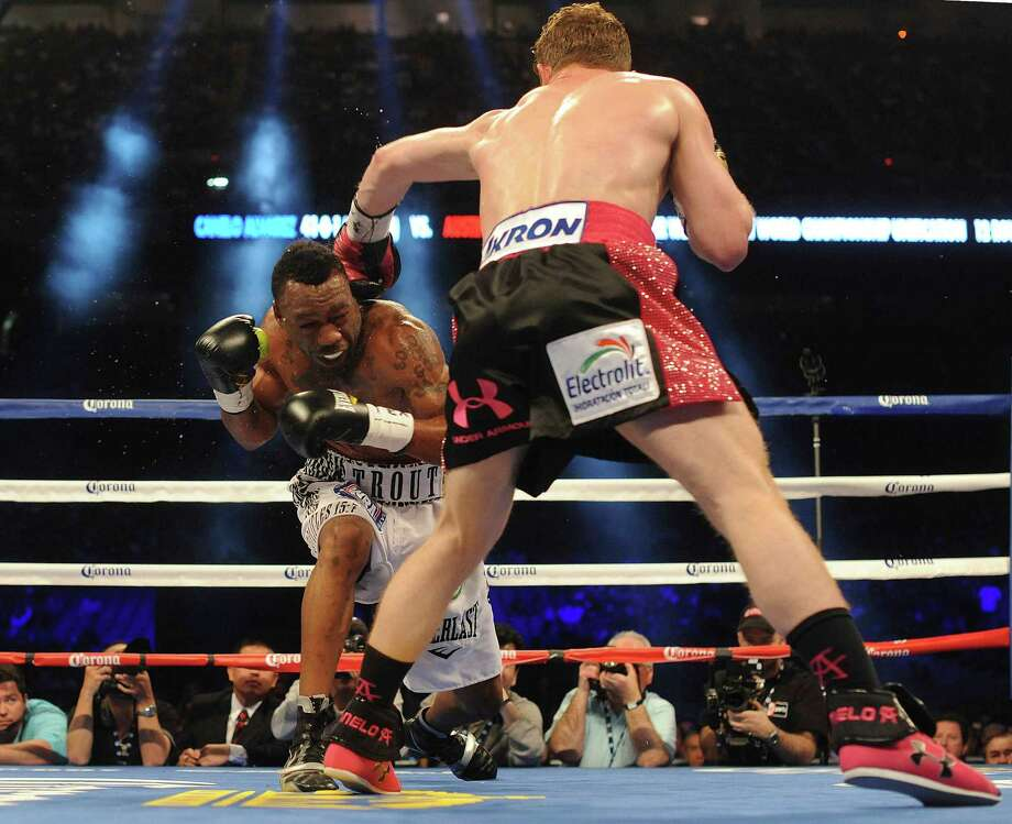 "Austin Trout receives a blow r4om Saul ""Canelo"" Alvarez during the 2nd round of their 154-pound boxing title unification bout in the Alamodome on Saturday, April 20, 2013. Photo: Billy Calzada, Express-News / San Antonio Express-News"