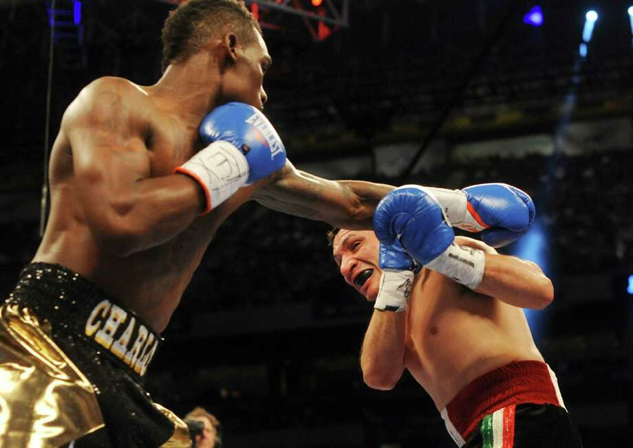 Jermall Charlo, left, swings at Orlando Lora during their super welterweight bout in the Alamodome on Saturday, April 20, 2013. Photo: Billy Calzada, Express-News / San Antonio Express-News