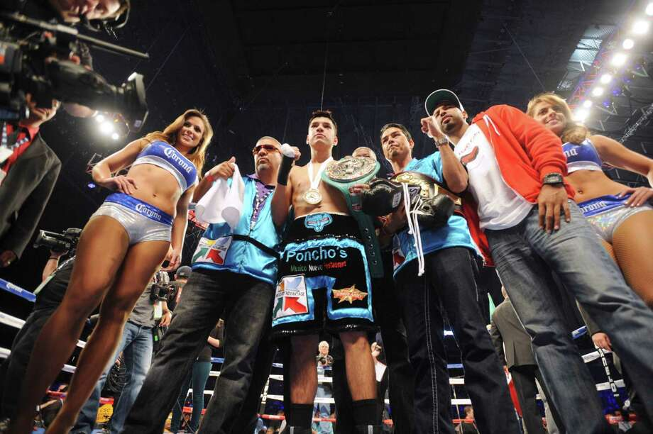Omar Figueroa displays his title belt after defeating Abner Cotto in the Alamodome on Saturday, April 20, 2013. Photo: Billy Calzada, Express-News / San Antonio Express-News