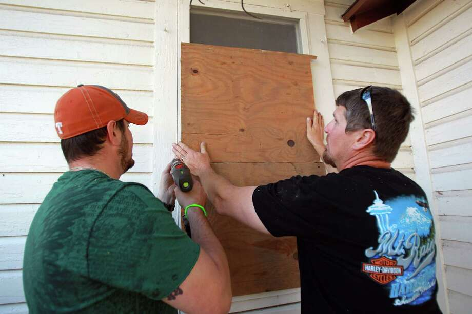 Matt Pavlicek, who lives in Sugar Land, and brother Chris Pavlicek board up a broken windows on Saturday, April 20, 2013, in West. Authorities are starting the re-entry process in phases, and this afternoon Phase I began by allowing residents into parts of West less devastated. Photo: Mayra Beltran, Houston Chronicle / © 2013 Houston Chronicle