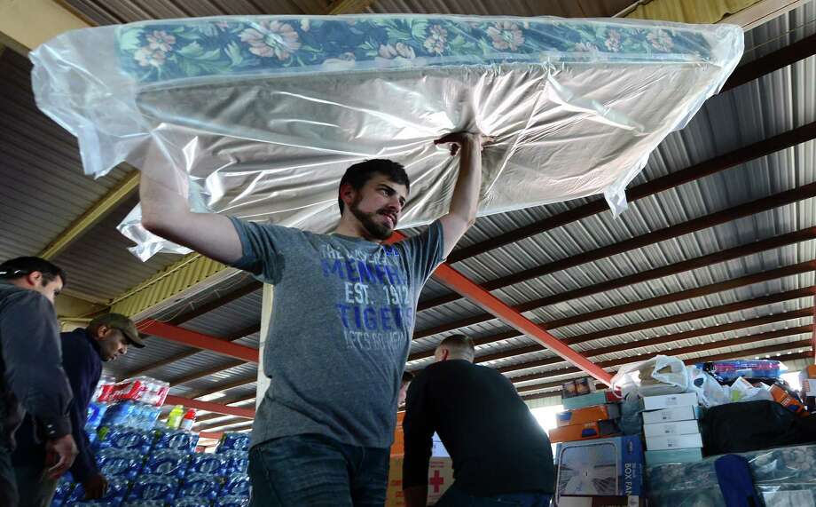 A volunteer carries a mattress to load onto a truck at a distribution center where supplies like water and clothing, including medical supplies, are being dropped off or picked up as needed, in West, Texas, on April 19 2013, two days after a deadly fertilizer plant blast occured.  While rescuers in Texas were set to return to the rubble in their continuing search for survivors after the massive blast killed as many as 15 people and destroyed dozens of homes, all roads leading to the area of destruction have been closed off and manned by various state authorities controlling the entry and exit of vehicles and people.AFP PHOTO/Frederic J. BROWNFREDERIC J. BROWN/AFP/Getty Images Photo: FREDERIC J. BROWN, AFP/Getty Images / AFP
