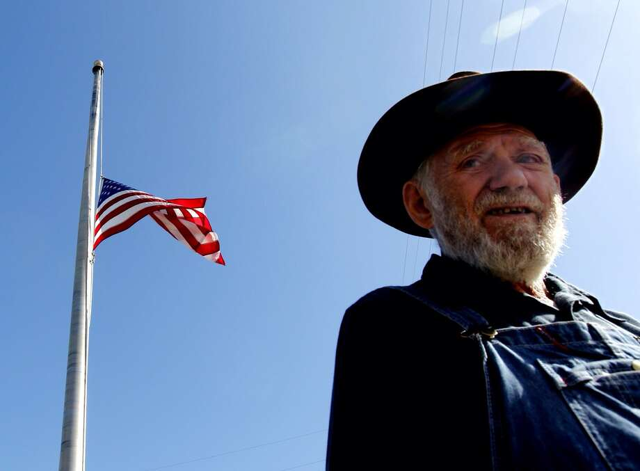 A resident just outside West, Joe Dvorak walks past a flag at half mast outside the post office. Photo: Johnny Hanson
