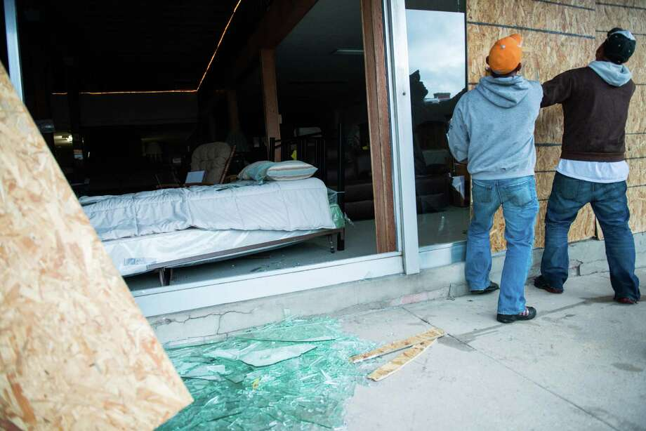 Workers place board over the broken windows of West Furniture on Thursday morning. Photo: Smiley N. Pool, Houston Chronicle / © 2013  Houston Chronicle