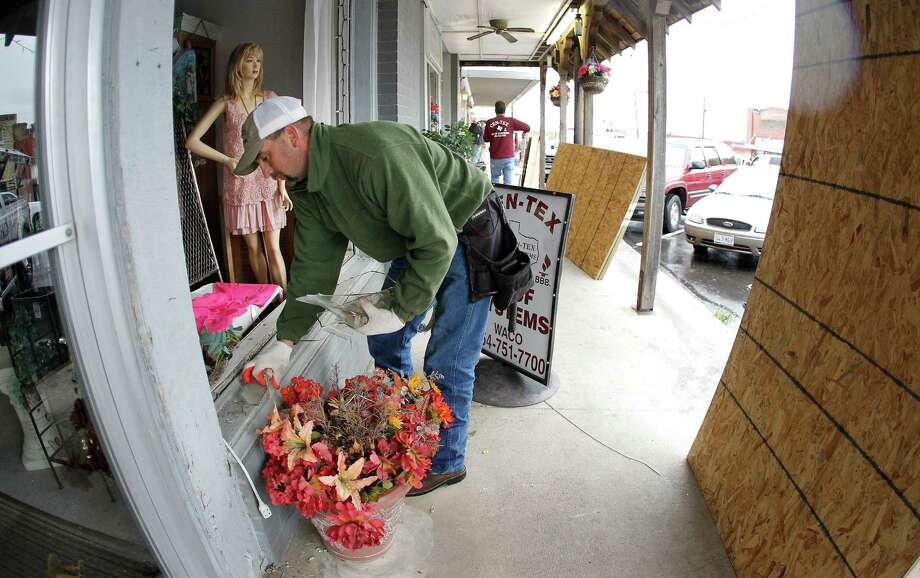 Shane Northcutt removes shattered glass from the display windows of The Village Shoppe in West, Texas on Thursday, April 18, 2013. A massive explosion at the West Fertilizer Co. killed as many as 15 people and injured more than 160, officials said overnight.  The explosion that struck around 8 p.m. Wednesday, sent flames shooting into the night sky and rained burning embers and debris down on shocked and frightened residents. Photo: Paul Moseley, AP / The Fort Worth Star-Telegram