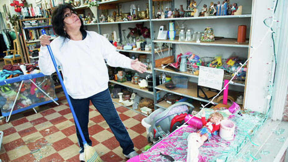 Maria Galvan cleans up broken glass from the blown out front windows of the West Thirft Shop  on Thursday morning, April 18, 2013, in West, Texas.  A massive explosion at a fertilizer plant killed as many as 15 people and injured more than 160, officials said overnight. Photo: Smiley N. Pool, . / © 2013  Houston Chronicle