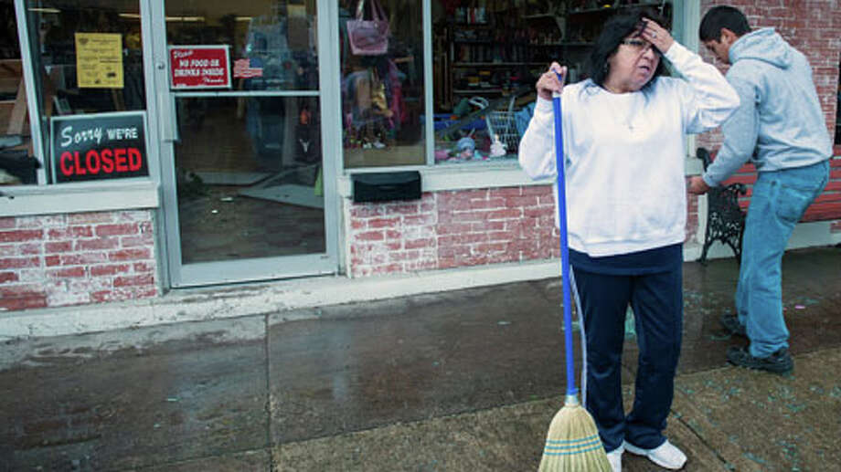 Maria Galvan pauses while sweeping up broken glass from the blown out front windows of the West Thirft Shop  on Thursday morning, April 18, 2013, in West, Texas.  A massive explosion at a fertilizer plant killed as many as 15 people and injured more than 160, officials said overnight. Photo: Smiley N. Pool, . / © 2013  Houston Chronicle