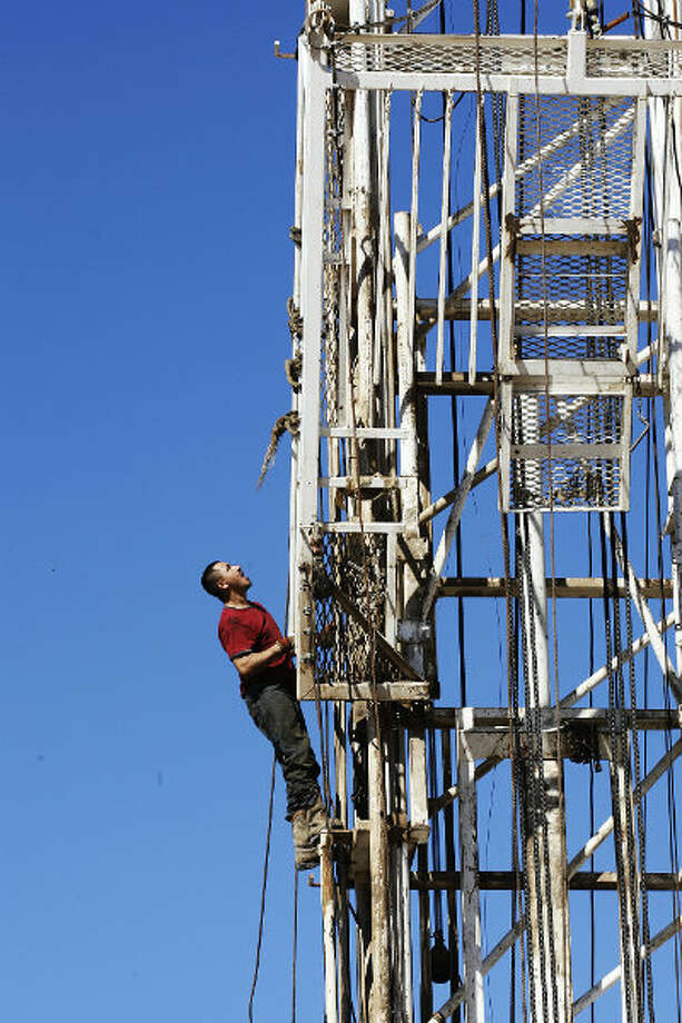 Anatolio Salinas climbs up the rig as it is erected and prepared for drilling at the site. The main area of interest was a formation called the San Miguel Sandstone. Photo: Jerry Lara, San Antonio Express-News