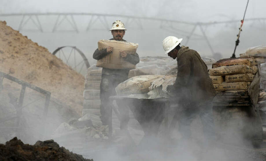 Derrickman Nestor Lerma, right, gets help mixing mud from floorhand J.B. Espinoza, 21, of Freer. The chemicals were used to manage the consistency of the mud that built up the walls of the hole being drilled. Photo: Jerry Lara, San Antonio Express-News