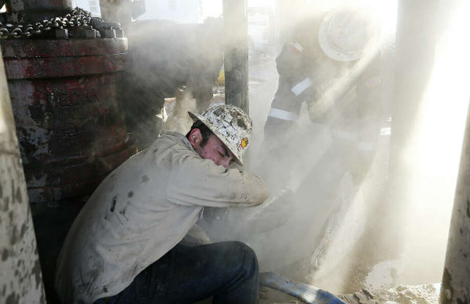 Floorhand J.B. Espinoza covers himself as calcium chloride is used to speed up the hardening of a cement base before installing blowout prevention equipment. Photo: Jerry Lara, San Antonio Express-News