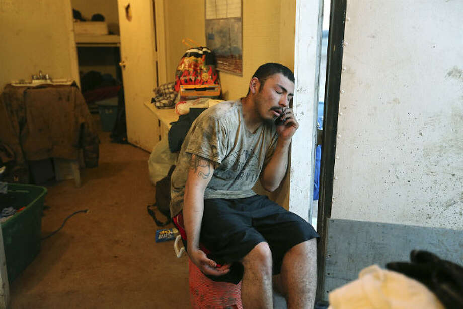After his shift, floorhand J.B. Espinoza, 21, calls his girlfriend while waiting for his turn to shower inside the company-provided housing at a drilling site in Frio County, Sunday, Jan. 20, 2013. It was Espinoza's first week on the rig. Photo: Jerry Lara, San Antonio Express-News