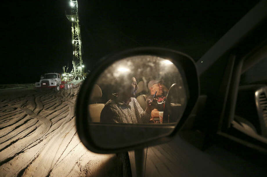 "Smoking cigarettes, checking out Facebook and talking with spouses, derrickman Nestor Lerma, Jr., 36, of Freer, left, and driller Humberto Hinojosa, 51, of Benavides, watch the drilling rig after their 12-hour shift. ""There's nothing here to do, we don't have television, so we watch the rig, "" said Lerma. Photo: Jerry Lara, San Antonio Express-News"