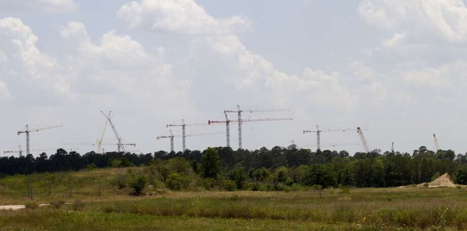 Construction cranes rise above the trees last June at the site of Exxon Mobil\'s campus.