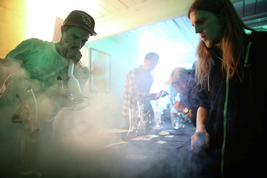 "Nick Villejo of Refine Cooperative and Jared Smith, right, smoke marijuana during ""Studio 4/20,"" a legal marijuana celebration put on by DOPE Magazine at 7 Point Studios on April 20, 2013 in Seattle. The event billed itself as the largest local marijuana celebration since pot was legalized by Washington voters. The state is still working on rules for growing and distribution of legal pot.Related article: What happens when you throw a big legal marijuana party in Seattle? Photo: JOSHUA TRUJILLO, SEATTLEPI.COM / SEATTLEPI.COM"