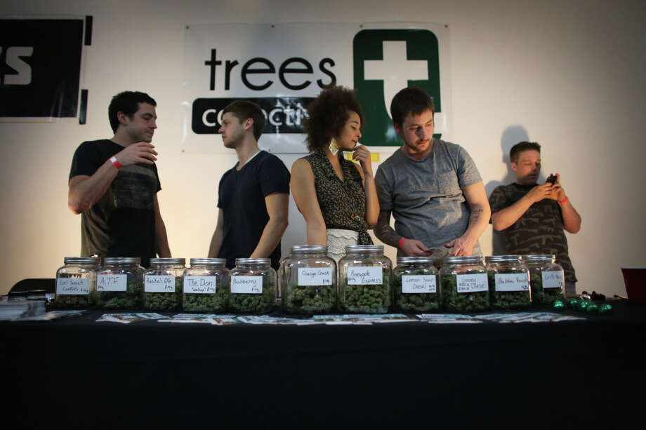 "From left, Sam Carroll, Ross Skocilich, Aubrey McMillan and Sam LaQuet of Trees Collective work their booth, selling their product during ""Studio 4/20,"" a legal marijuana celebration put on by DOPE Magazine at 7 Point Studios on April 20, 2013 in Seattle. Photo: JOSHUA TRUJILLO, SEATTLEPI.COM / SEATTLEPI.COM"