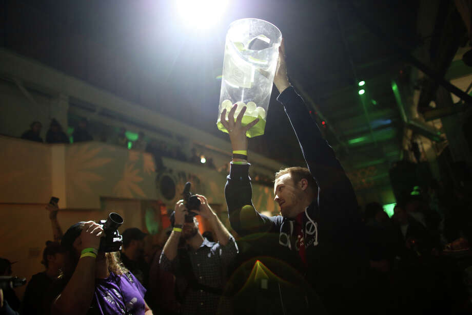 "Nathan Chrysler of DOPE Magazine hoists a container with the winning number of votes for the people's choice marijuana strain during ""Studio 4/20,"" a legal marijuana celebration in Seattle. Photo: JOSHUA TRUJILLO, SEATTLEPI.COM / SEATTLEPI.COM"
