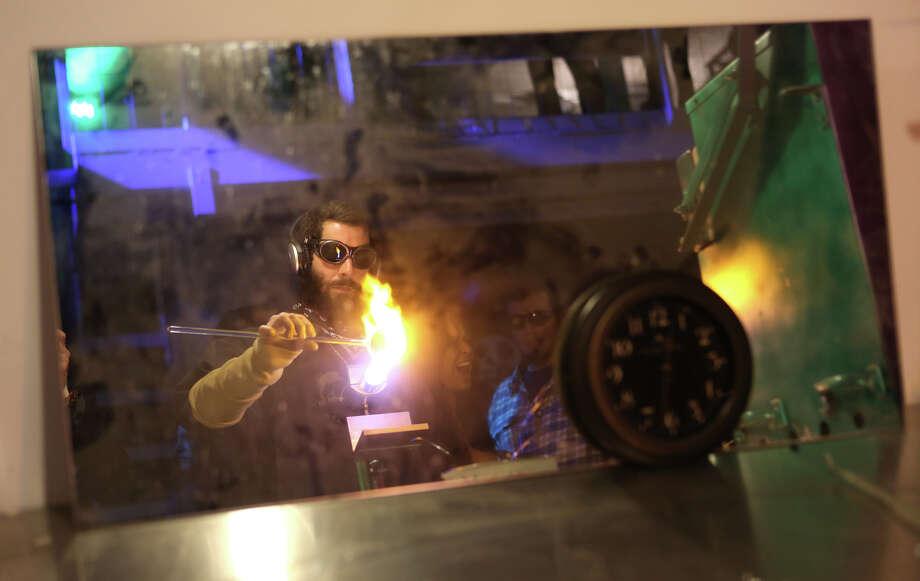 "Brock Marvel works on glass art, as seen in a mirror, during ""Studio 4/20."" Photo: JOSHUA TRUJILLO, SEATTLEPI.COM / SEATTLEPI.COM"
