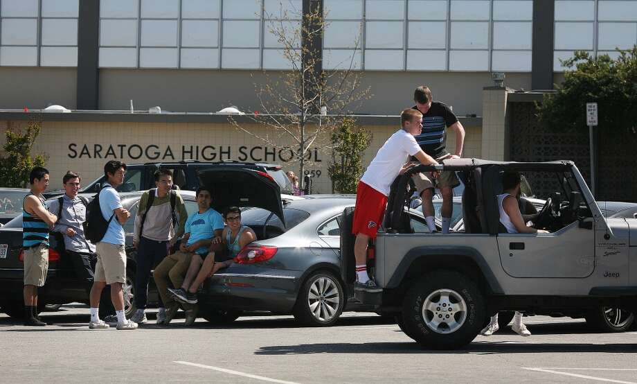 Teenage boys from Saratoga High School relax in the parking lot after school on Friday, April 12. Three arrests were made in connection to the suicide of a 16-year-old after she was sexually assaulted last fall.
