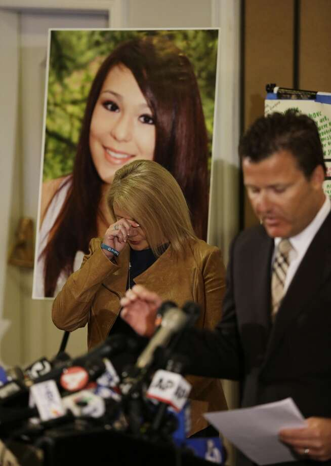 Sheila Pott, wipes her eyes standing in front of a photograph of her daughter Audrie Pott,  who committed suicide after a sexual assault as family representative Robert Allard, right, reads a statement during a news conference Monday, April 15, 2013 in San Jose, Calif. They said they were outraged by what they see as a refusal to take responsibility by the three boys arrested in the attack on the 15-year-old girl in Saratoga, a bedroom community on the fringe of Silicon Valley.