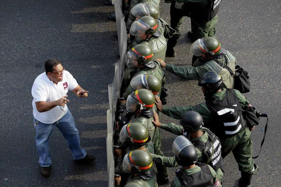 An opposition supporter confronts riot police along a highway in the Altamira neighborhood of Caracas, Venezuela, Monday, April 15, 2013. National Guard troops fired tear gas and plastic bullets to disperse students protesting the official results in Venezuela's disputed presidential election. Photo: AP