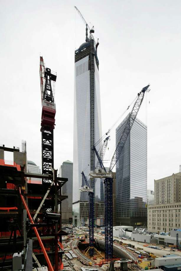 Construction cranes, center, work over the transportation hub at the World Trade Center, Thursday, April 18, 2013 in New York. At left is Three World Trade Center and One World Trade Center rises over the site. Photo: AP