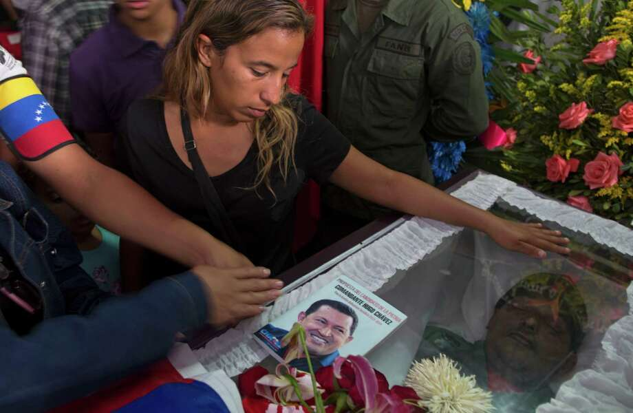 Elvira Guzman mourns over the body of her husband, 45-year-old Jose Luis Ponce, a Chavista militant who was allegedly killed on Monday in a confrontation with opposition supporters, as another person places an image of Chavez on his coffin during his wake in Caracas, Venezuela, Wednesday, April 17, 2013.  The political heirs of Hugo Chavez filled Venezuela's airways Wednesday with a steady drumbeat of attacks on the man who says they stole the presidency from him. They called opposition leader Henrique Capriles a coup-plotter and said he was inciting post-election violence that had claimed seven lives, including Ponce, and injured 61. Capriles called the government assault a smoke screen to divert attention from his demand for a recount of every ballot from Sunday's election. Photo: AP