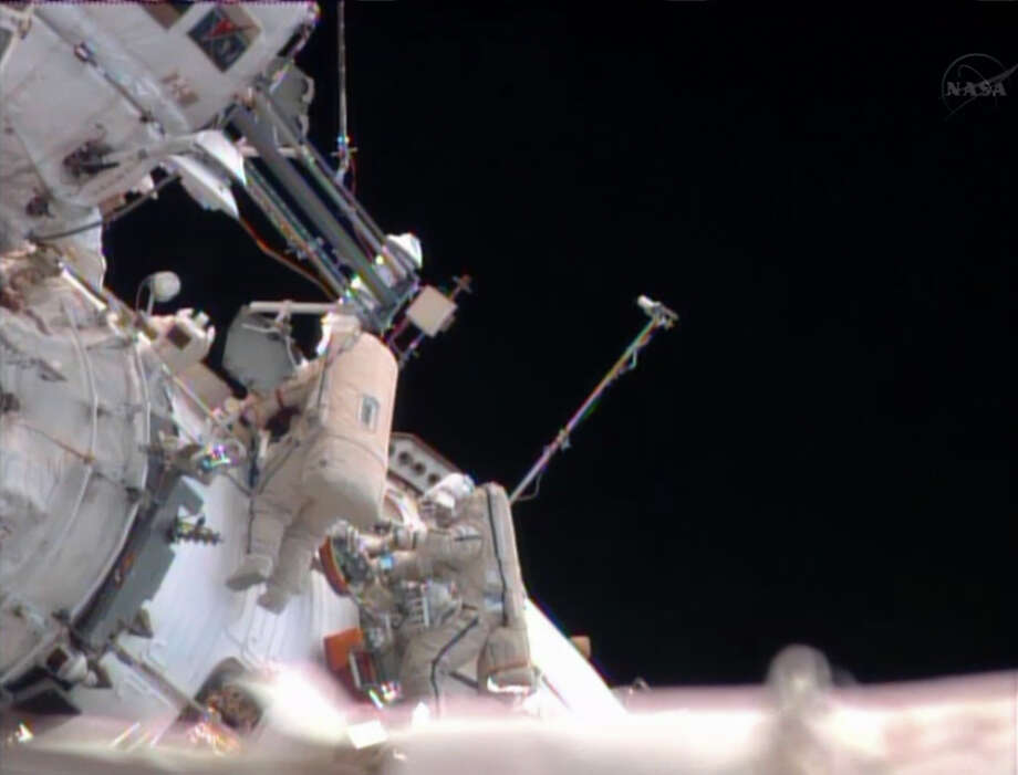 In this image made from video provided by NASA, Russian cosmonauts Pavel Vinogradov, left, and Roman Romanenko perform a spacewalk outside the International Space Station to gather old science experiments and install new ones, and replace a navigation device. Photo: AP