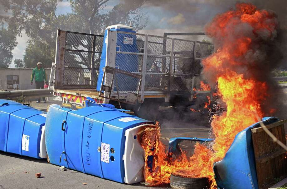A truck that carried  temporary plastic toilets burns near Khayelitsha township on the outskirts of  Cape Town, South Africa, Thursday, April 18, 2013. The N2 highway leading into Cape Town city and past t Cape Town airport  had to be closed as locals protested against the lack on services in the township. They had been demanding that brick built toilet facilities be built in the township.  (AP Photo/Schalk van Zuydam)   service delivery Photo: AP