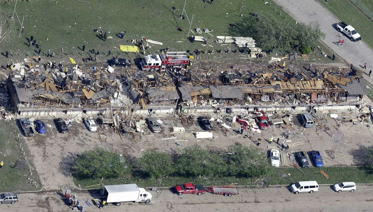 In this Thursday, April 18, 2013 aerial photo, emergency personnel investigate the scene of an apartment complex destroyed by an explosion at the West Fertilizer Co. in West, Texas. Rescuers searched the smoking remnants for survivors of a thunderous fertilizer plant explosion. It killed 15 people including 12 first responders, and trapped 133 people in the rubble of their nursing home. More than 250 people were hurt.